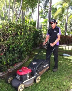 mowing a lawn close to a hedge