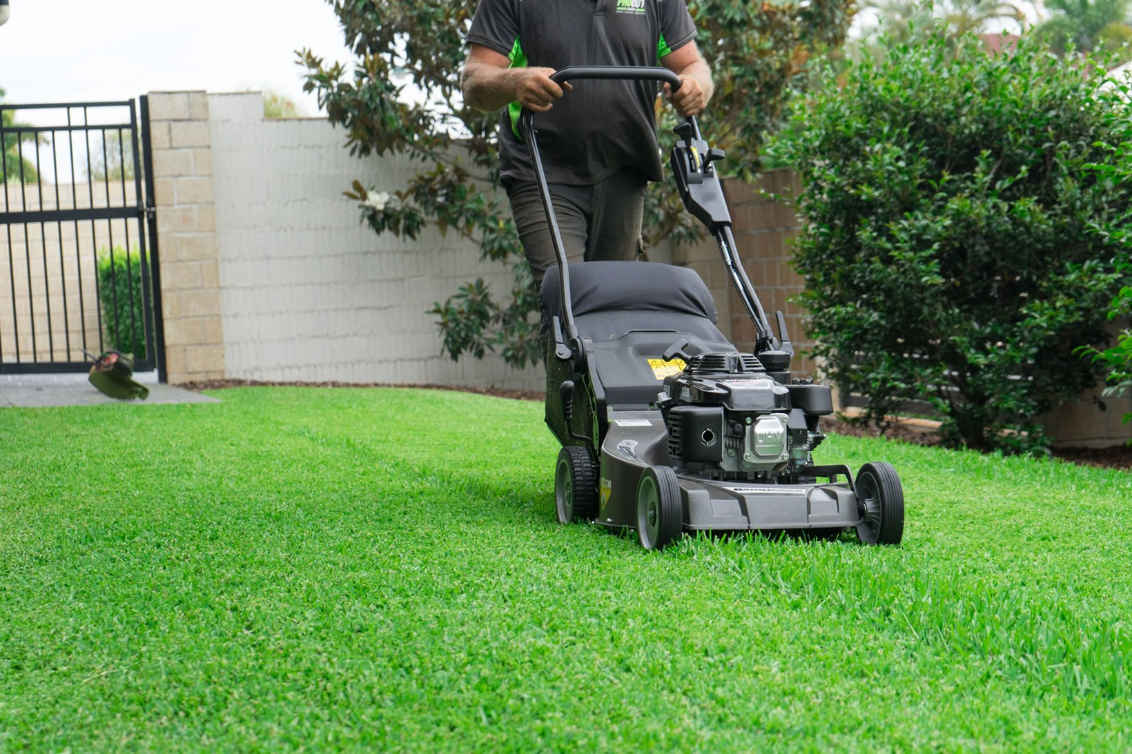 pro cut lawns operator pushing a lawn mower