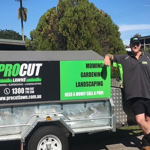 bribie island operator standing next to pro cut lawns trailer with gardening equipment